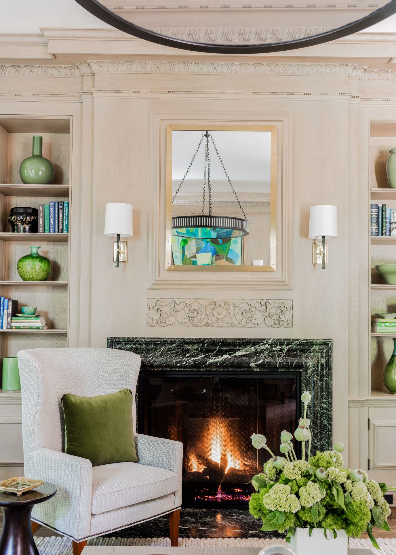 transitional living room, wall niche, built in bookcase, wood burning fireplace, transtional fireplace surround, contemporary chandelier, aged iron chandelier, transitional chandelier, applied wall moulding, transitional wall sconces, green marble fireplace surround